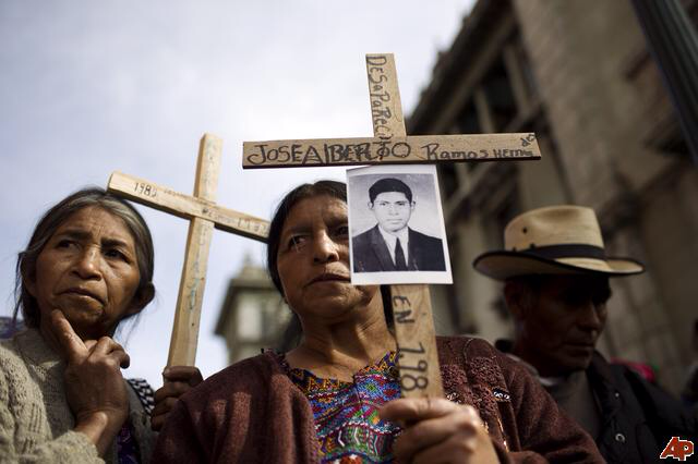Mayans hold crosses, with photo of victim of Guatemala civil war
